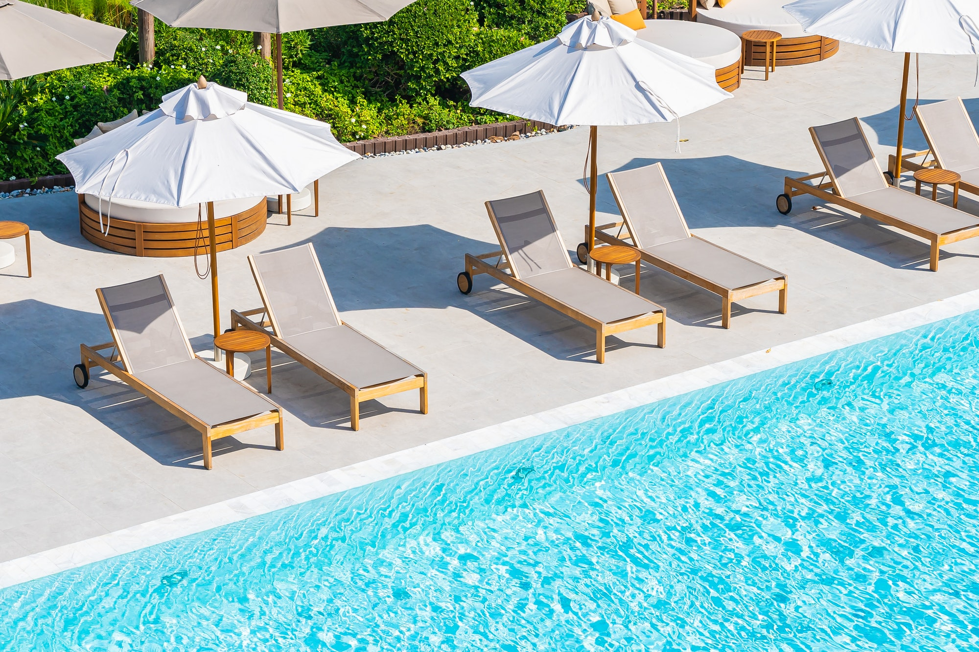 Umbrella and deck chair around outdoor swimming pool in hotel resort